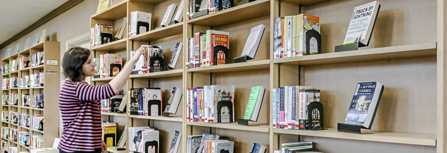 Woman browsing bookshelves containing bestsellers