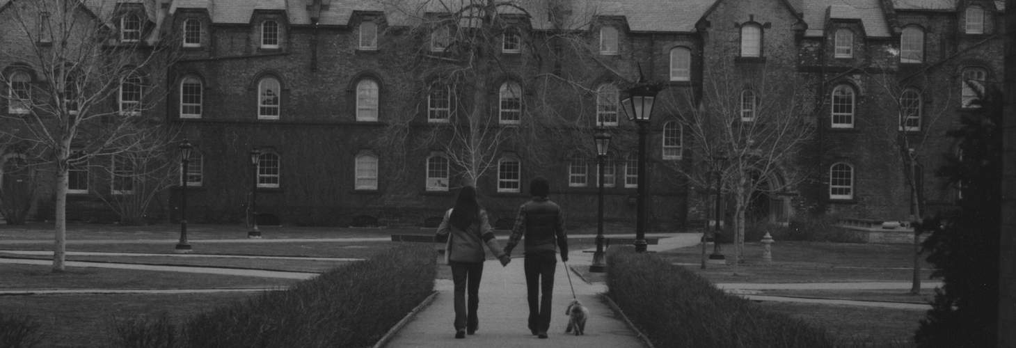 Two people walking with a dog, seen through an archway, with University College in background