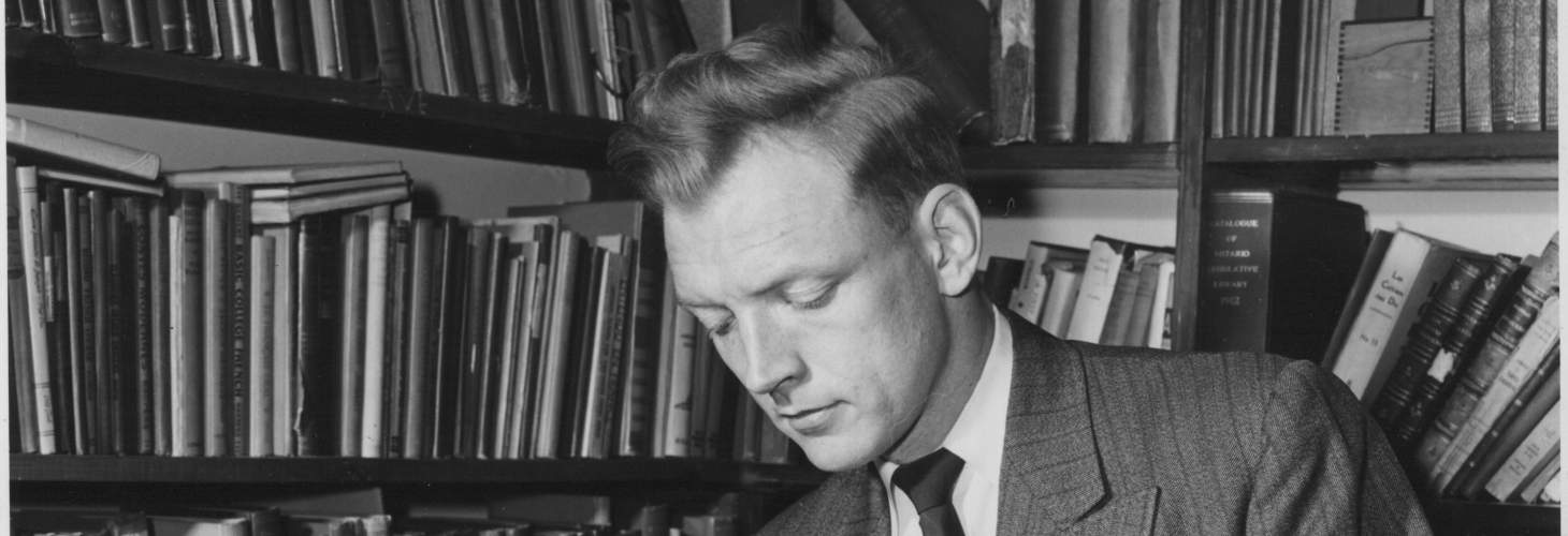 David Hayne, wearing a suit, reading a book in front of a bookcase