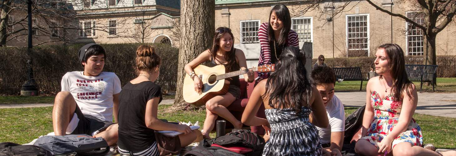 Students in group listening to woman playing guitar