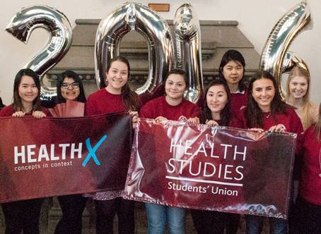 Students holding a Health Studies banner in front of reflective balloons