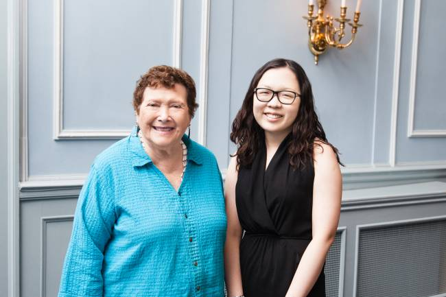 UC donor Crystal Hawk standing next to UC student Abby Chu in a banquet hall.