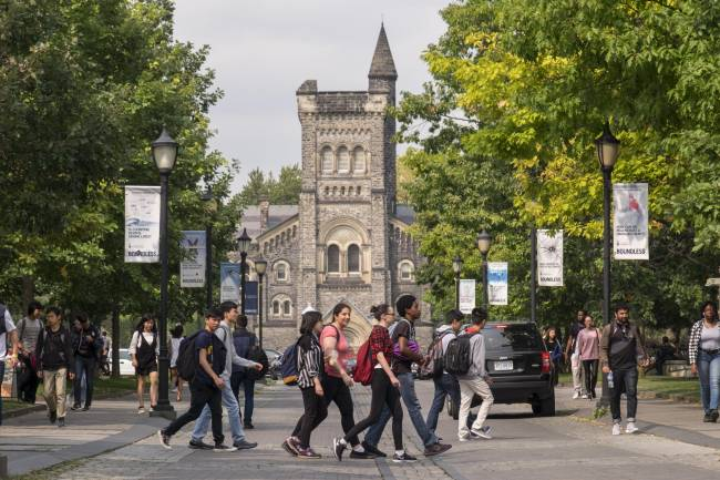 Group of student walking across front entrance of U of T with University College in the background