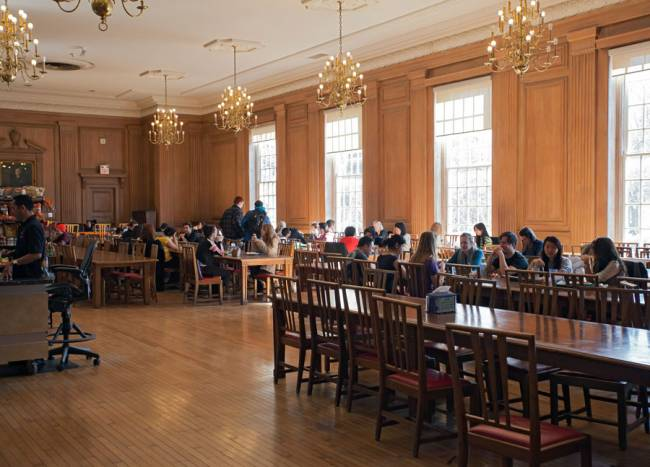students eating on tables in a dining hall