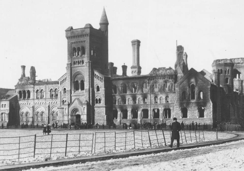 University College damaged by fire, with dozens of people and two horse-drawn carriages in front of the building