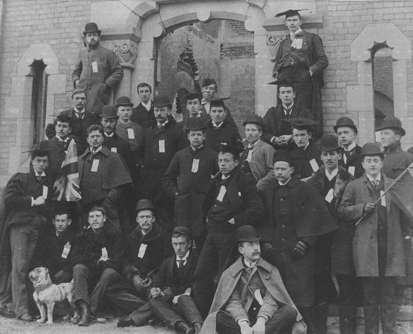 Group of about 30 men, and a small bulldog, in front of University College