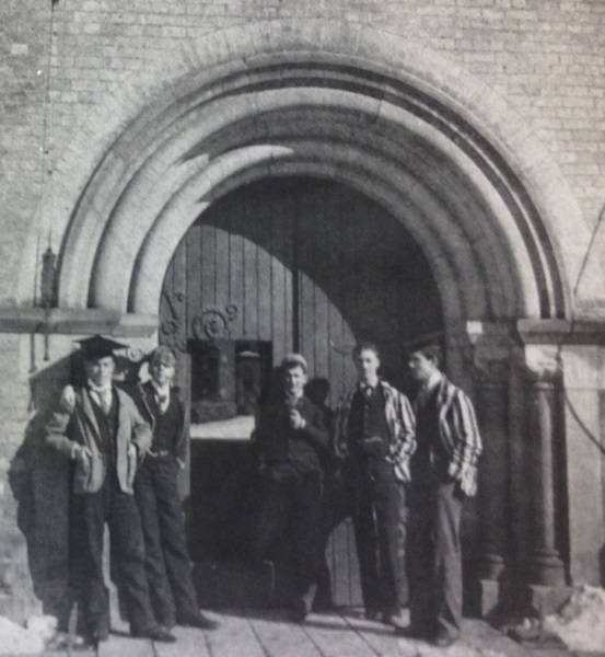 A young William Lyon Mackenzie King with four other young men, standing in front of arched doorway
