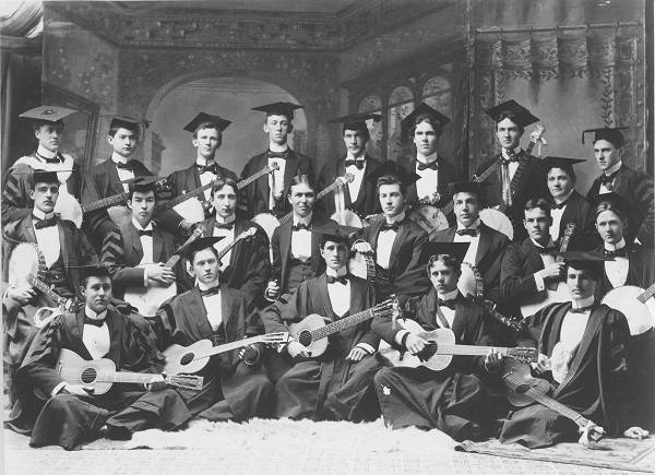 About 20 men, each holding a banjo or guitar, dressed in academic robes and mortarboards
