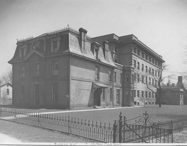 Exterior of building with lawn and wrought iron fence