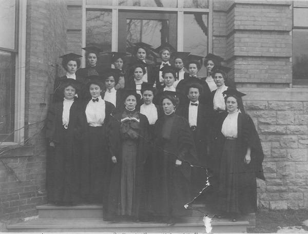 About 20 women posing in doorway of building, wearing academic robes and mortarboards