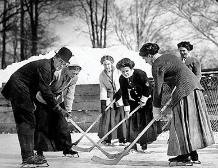 Five women playing ice hockey and a male official holding a hockey puck