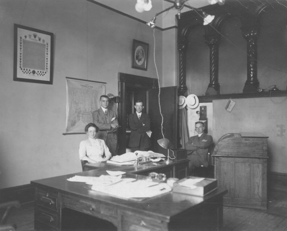 one woman and three men in an office
