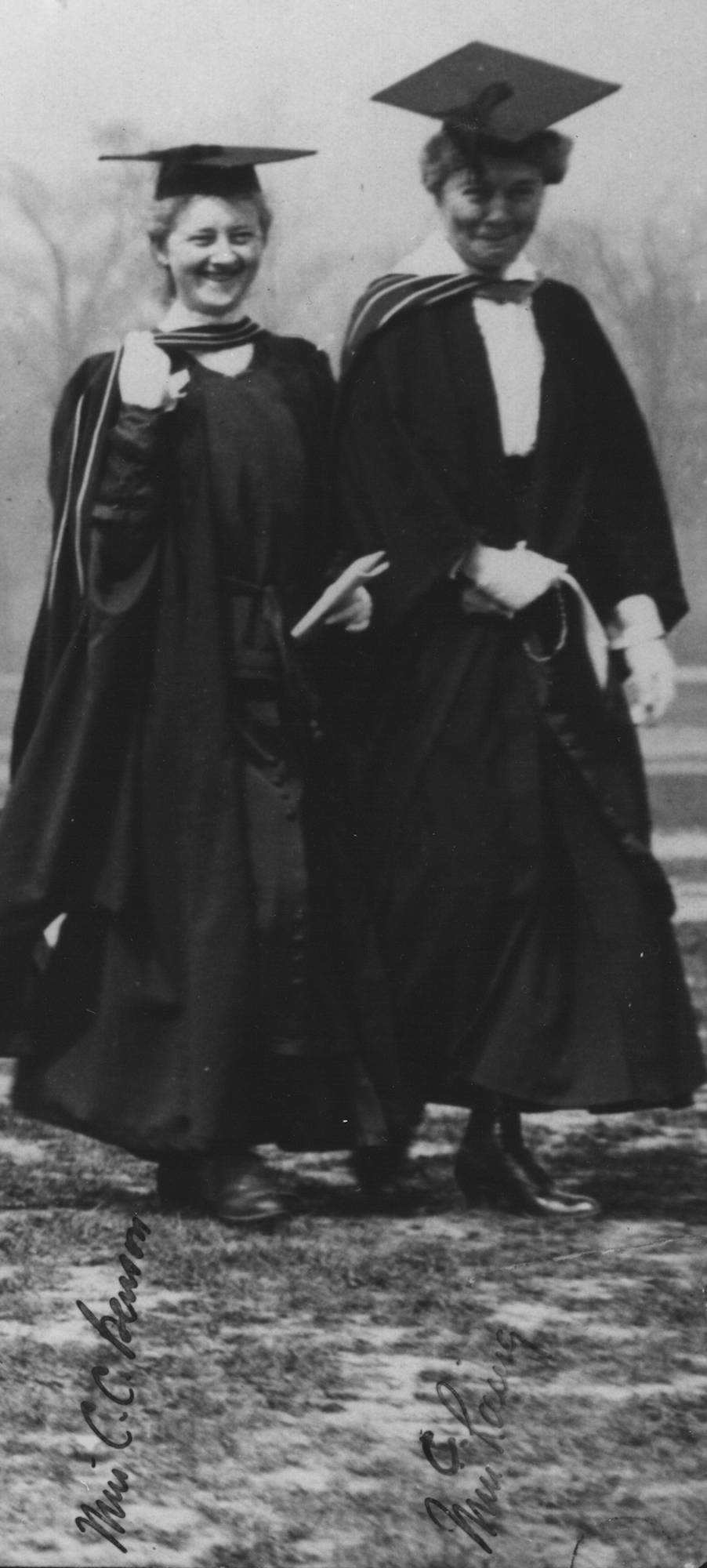 two women in academic robes and mortarbards, walking and smiling