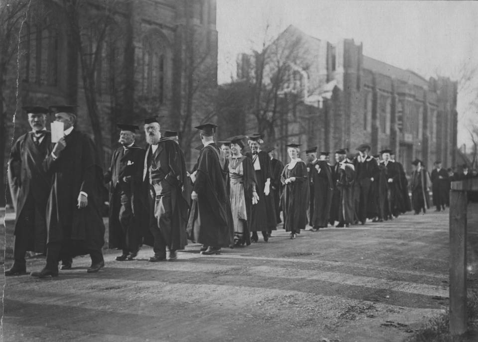 Over twenty people in academic robes walking in a procession