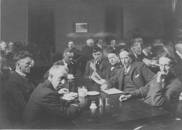 Eight men sitting around a table, with other men at tables in background