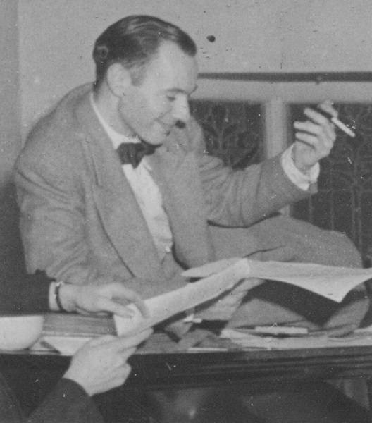 Man in suit with a cigarette in one hand and paper in the other, smiling