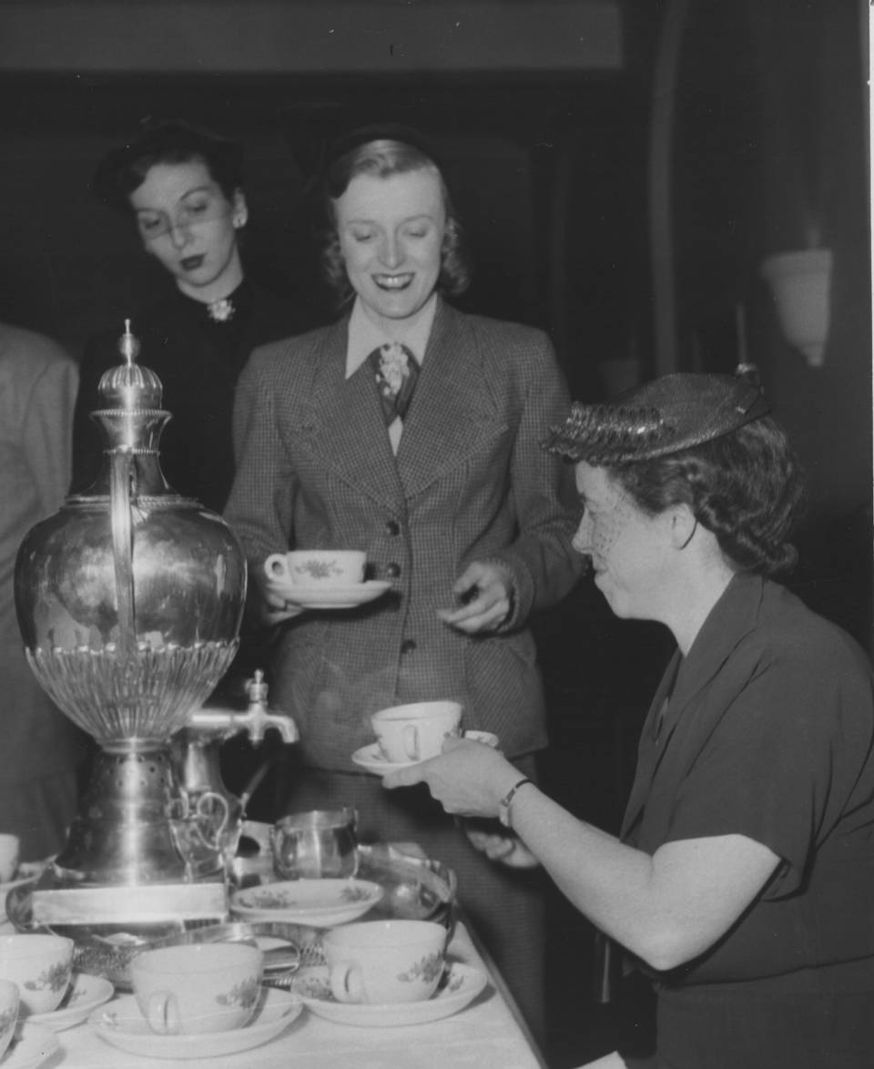 Woman serving tea from a samovar to two other women