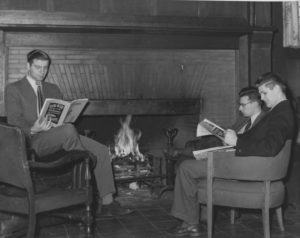 Three young men in suits reading magazines by the fire, in armchairs.