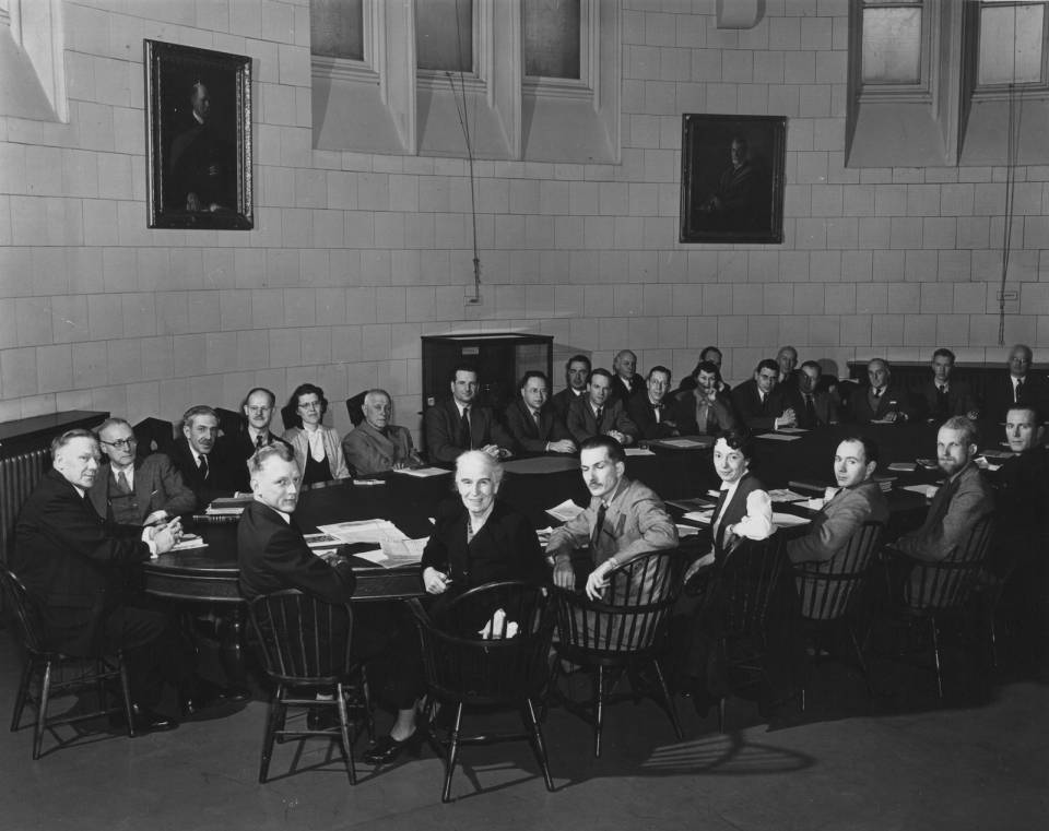 About thirty people sitting around a large oval table, including about four women