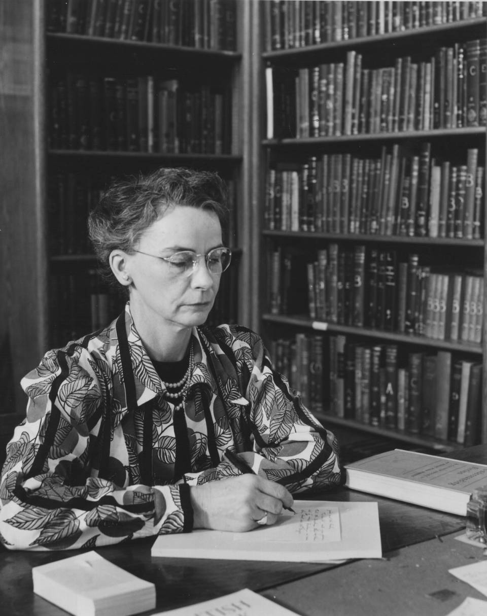 Margaret Hiltz working at desk, with shelves of books in the background