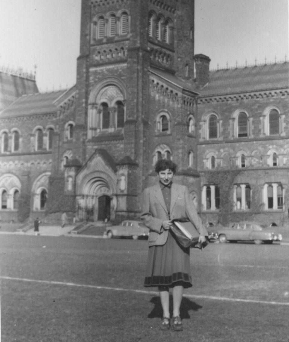 Woman standing on grass with University College in the background