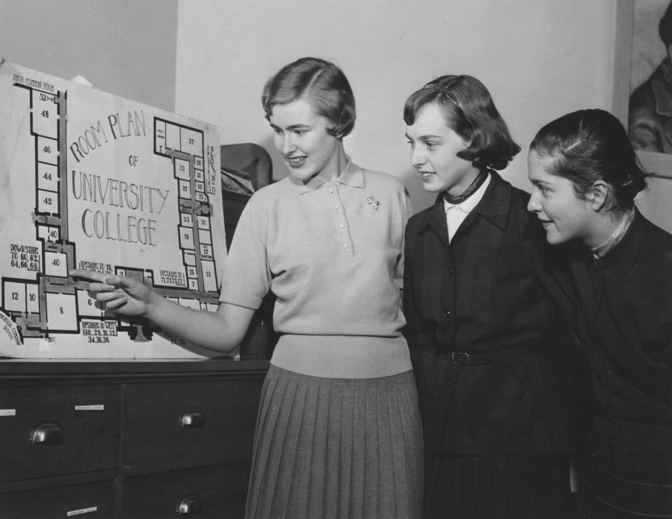 "Three young women looking at a ""Room Plan for University College"""