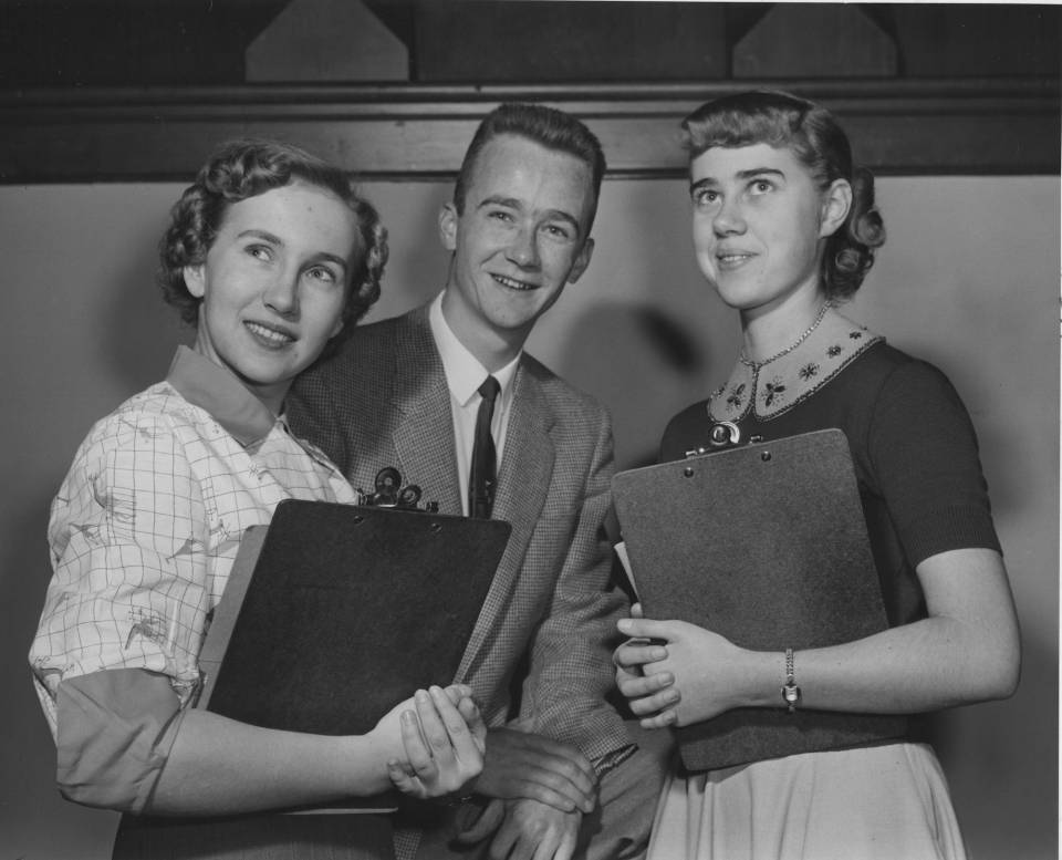 A young man and two young women holding clipboards