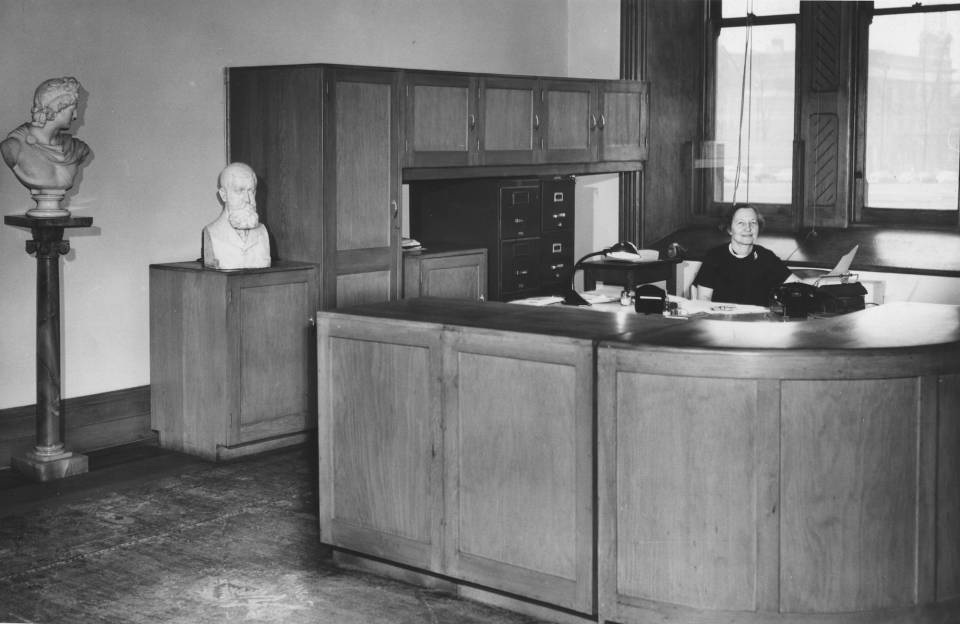 Woman seated behind large desk with counter