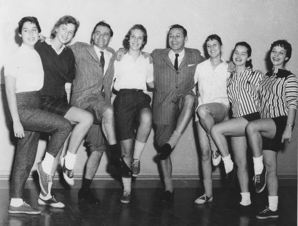 Johnny Wayne and Frank Shuster and six young women posing with one knee raised