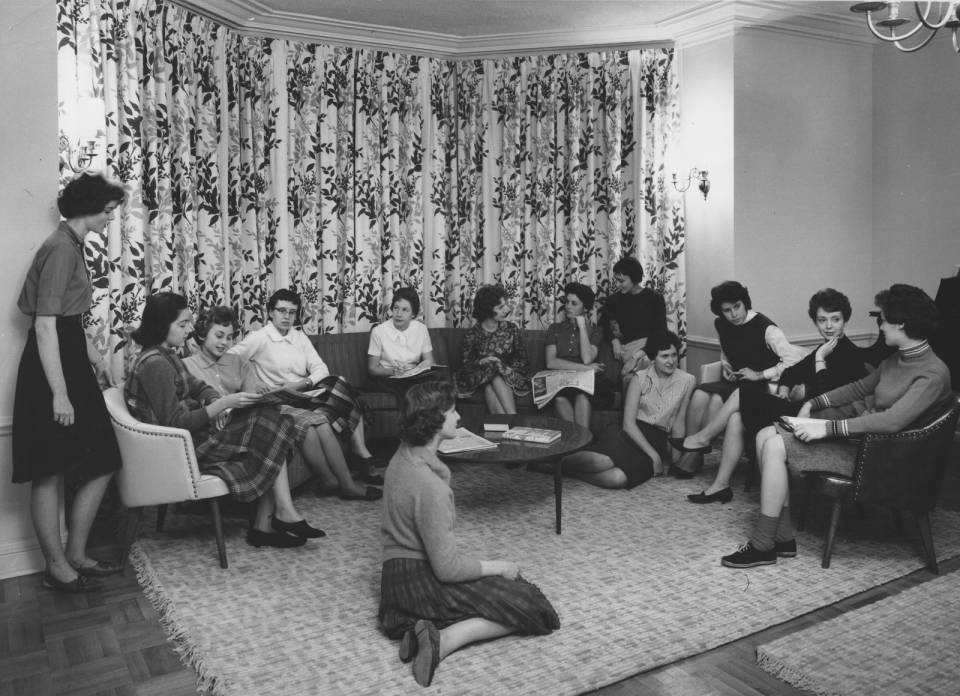 About thirteen young women sitting in a semi-circle.