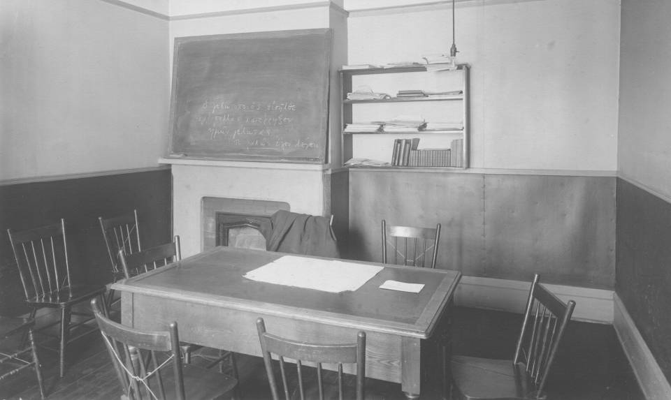 small room containing a table with wooden chairs, a blackboard with Greek writing, and a small bookshelf containing books and papers