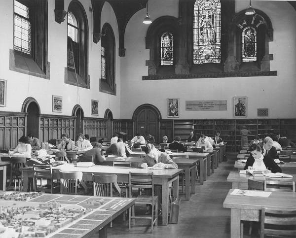 Students reading at tables and desks, with stained glass windows above