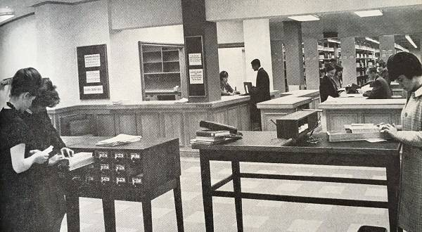 women looking in card catalogue, with two library service desks in background