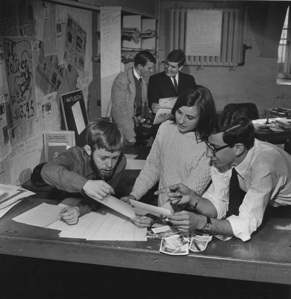 four men and one woman working on a magazine