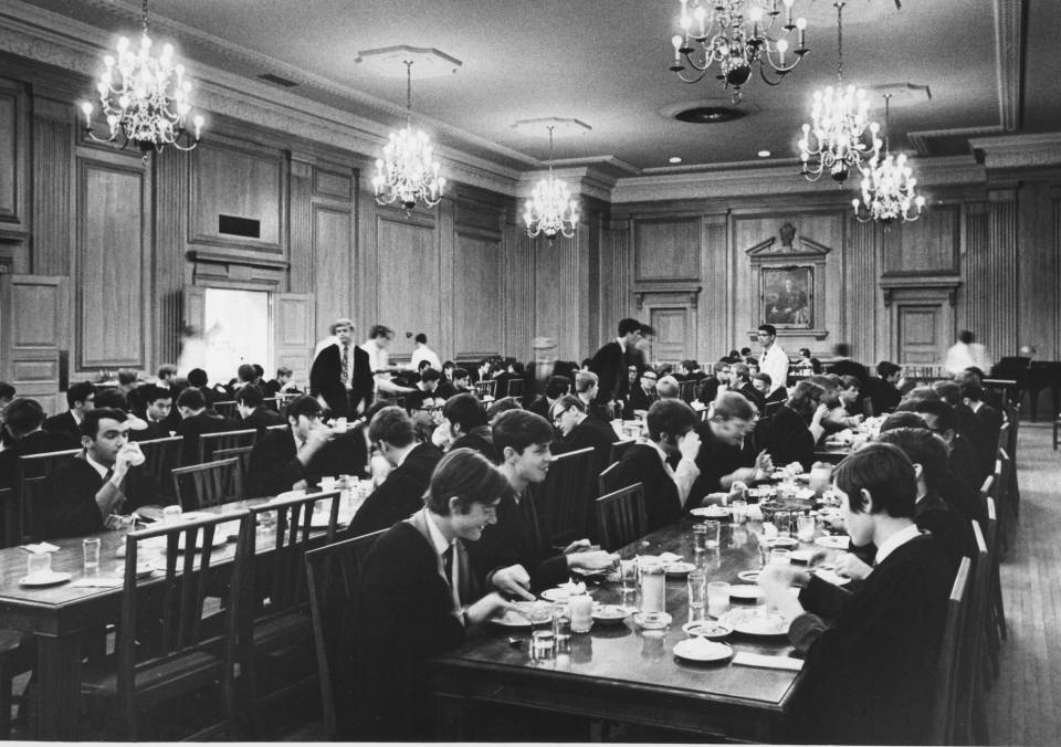 many young men in suits, ties, and academic robes, sitting at long dining tables, eating