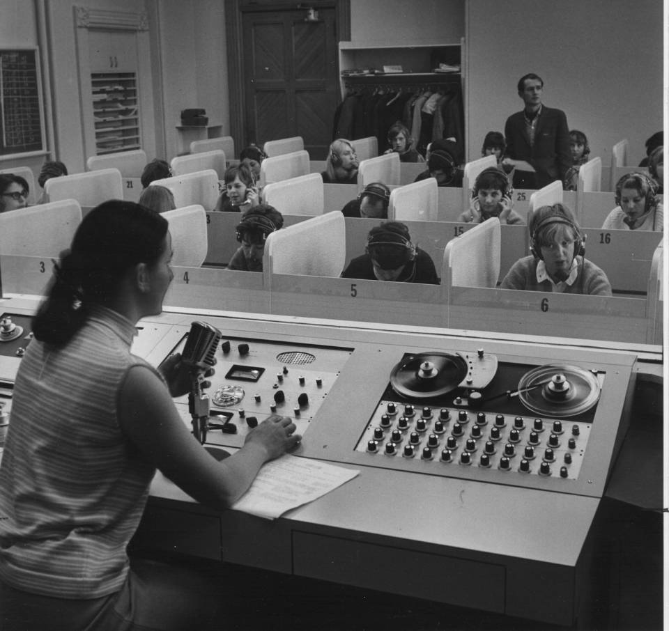 Two teachers and about fifteen students (with headphones) in a language lab