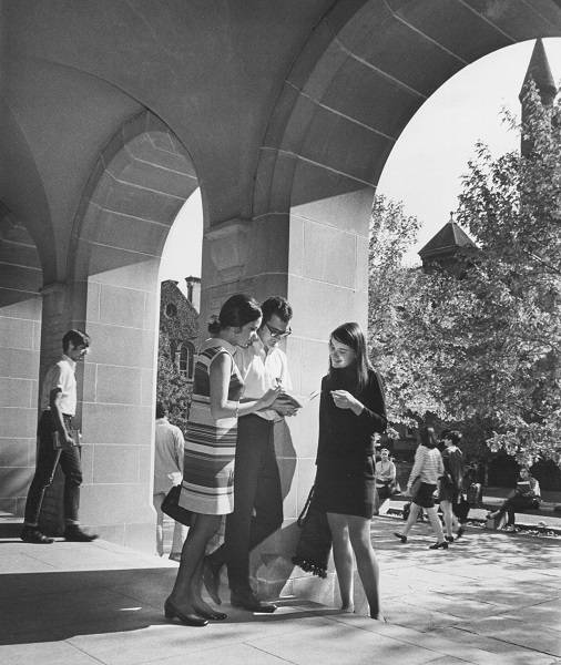 two young women and a young man looking at a book, with University College quadrangle and other students in background