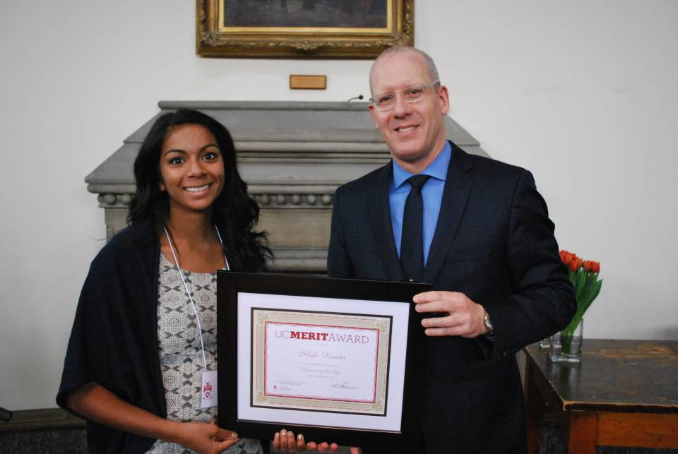Student holding UC Merit Award Plaque with Principal Donald Ainslie