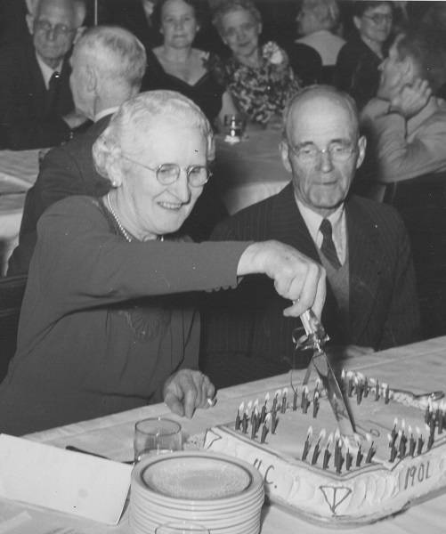 "Older woman cutting cake which says ""U.C. 1901"" while older man looks on"